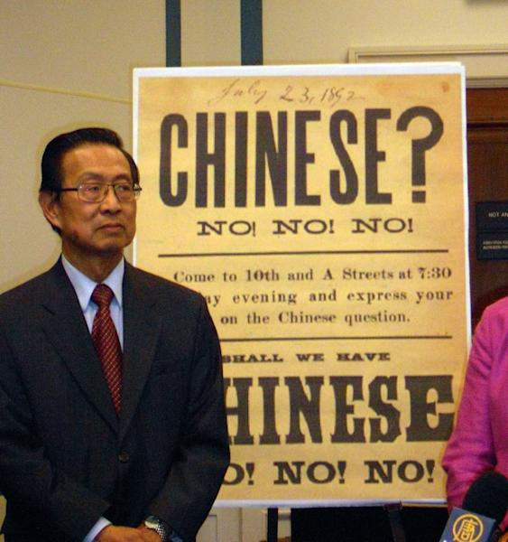 Michael Lin, chair of a coalition seeking a statement of regret over the 1882 Chinese Exclusion Act, speaks at a 2011 news conference in Washington in front of a reproduction of a 19th-century sign that aimed at rousing up sentiment against Chinese Americans