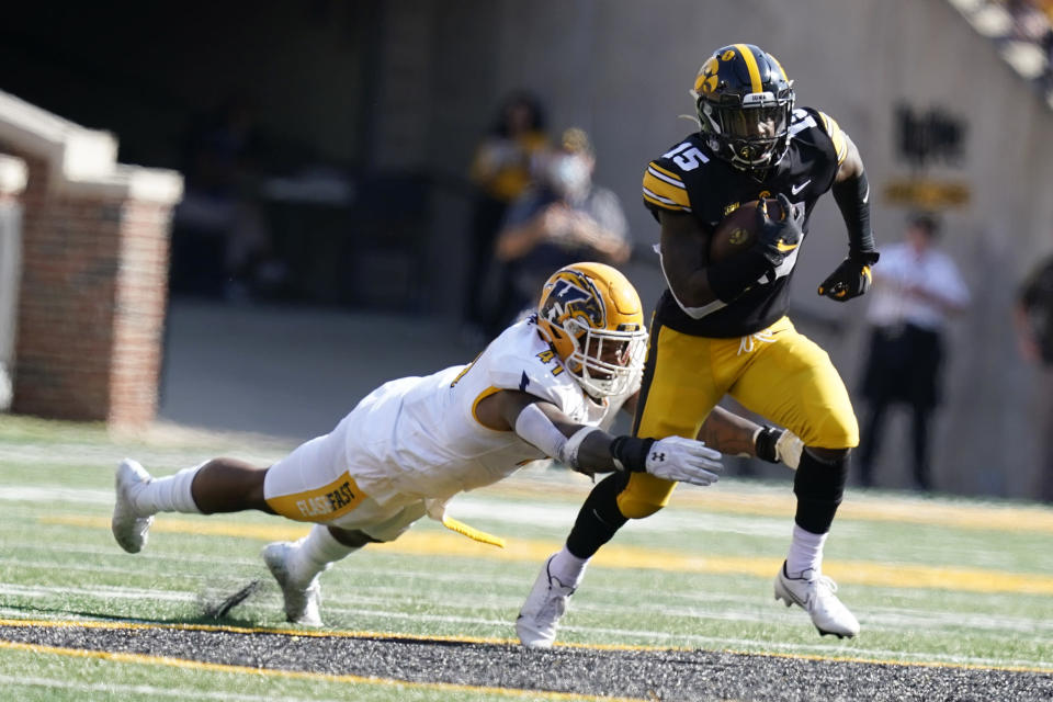 Iowa running back Tyler Goodson (15) runs from Kent State defensive lineman Jabbar Price (41) during the first half of an NCAA college football game, Saturday, Sept. 18, 2021, in Iowa City, Iowa. (AP Photo/Charlie Neibergall)