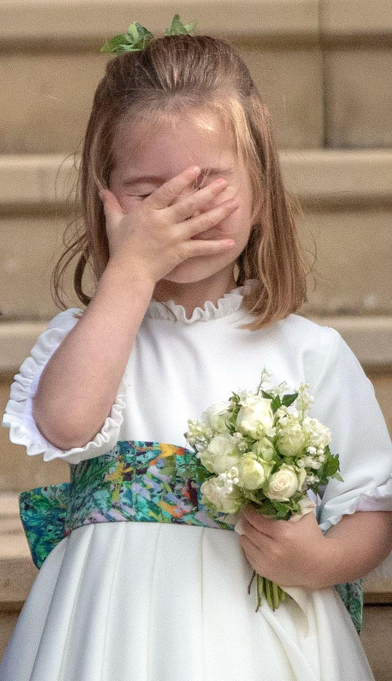 Britain's Princess Charlotte of Cambridge puts her hand on her face as she stands on the West Steps to wave off Britain's Princess Eugenie of York and Jack Brooksbank at St George's Chapel, Windsor Castle, in Windsor, on October 12, 2018 after their wedding ceremony. (Photo by Steve Parsons / POOL / AFP) (Photo credit should read STEVE PARSONS/AFP via Getty Images)