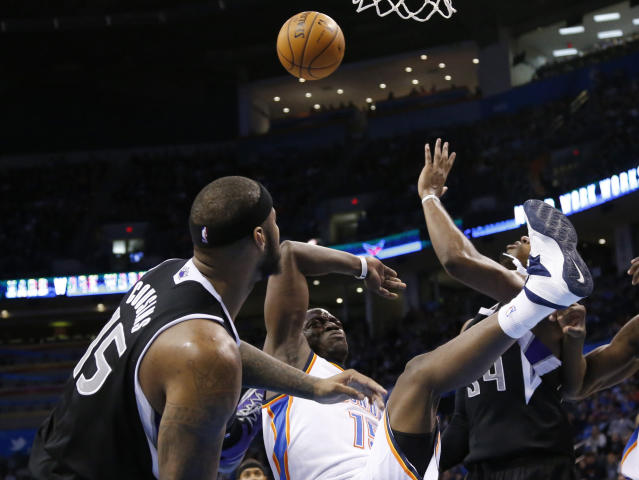 Oklahoma City Thunder guard Reggie Jackson (15) loses the ball and falls after being fouled by Sacramento Kings center DeMarcus Cousins (15) in the third quarter of an NBA basketball game in Oklahoma City, Sunday, Jan. 19, 2014. Oklahoma City won 108-93. (AP Photo/Sue Ogrocki)