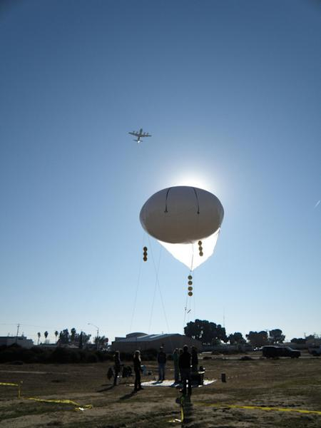 A NASA research plane flies over a tethered rheostat balloon in Huron, Calif., during a mission to improve air quality monitoring.
