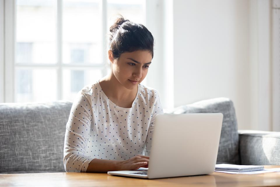 Focused Indian woman using laptop at home, looking at screen, chatting, reading or writing email, sitting on couch, serious female student doing homework, working on research project online