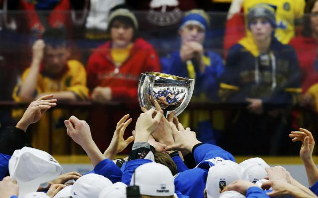 Young Sweden fans watch as Finland players celebrate with the trophy after they defeated Sweden in overtime of their IIHF World Junior Championship gold medal ice hockey game in Malmo, Sweden, January 5, 2014. REUTERS/Alexander Demianchuk (SWEDEN - Tags: SPORT ICE HOCKEY)