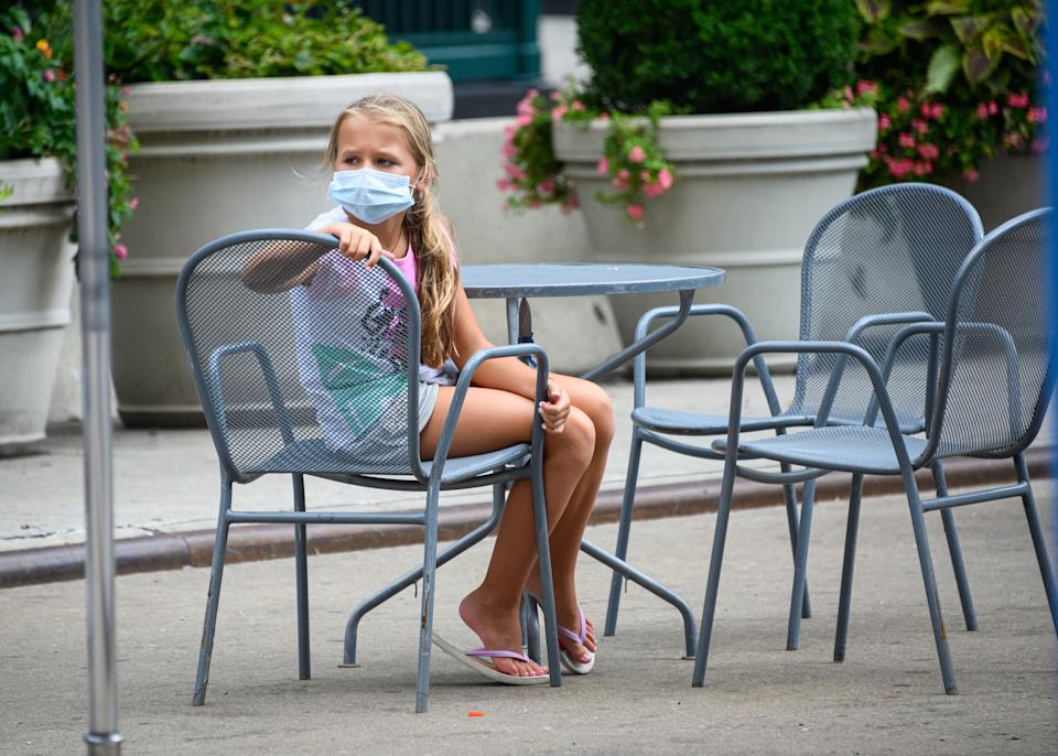 NEW YORK, NEW YORK - AUGUST 08: A kid wears a face mask at an outdoor restaurant seating the Flatiron district as the city continues Phase 4 of re-opening following restrictions imposed to slow the spread of coronavirus on August 8, 2020 in New York City. The fourth phase allows outdoor arts and entertainment, sporting events without fans and media production. (Photo by Noam Galai/Getty Images)