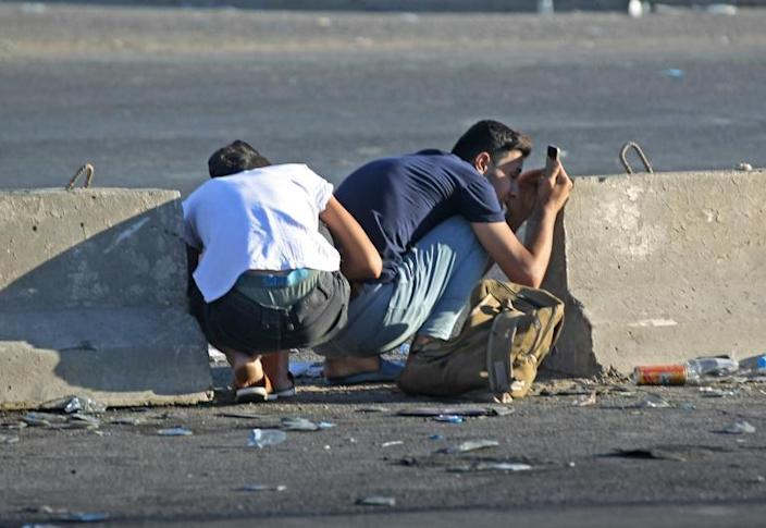 Iraqi protesters take cover in Baghdad's central Khellani Square, while using their mobile phones - devices that have been key to citizen efforts to record alleged heavy handed tactics by security forces (AFP Photo/AHMAD AL-RUBAYE)