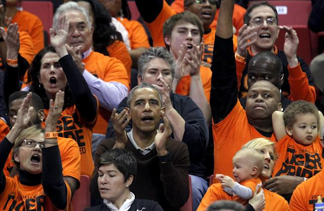 U.S. President Barack Obama (C) attends the game between Princeton and Green Bay for the 2015 Women's NCAA Basketball Tournament at the XFINITY Center in College Park, Maryland March 21, 2015. Obama's niece Leslie Robinson plays for Princeton. REUTERS/Yuri Gripas
