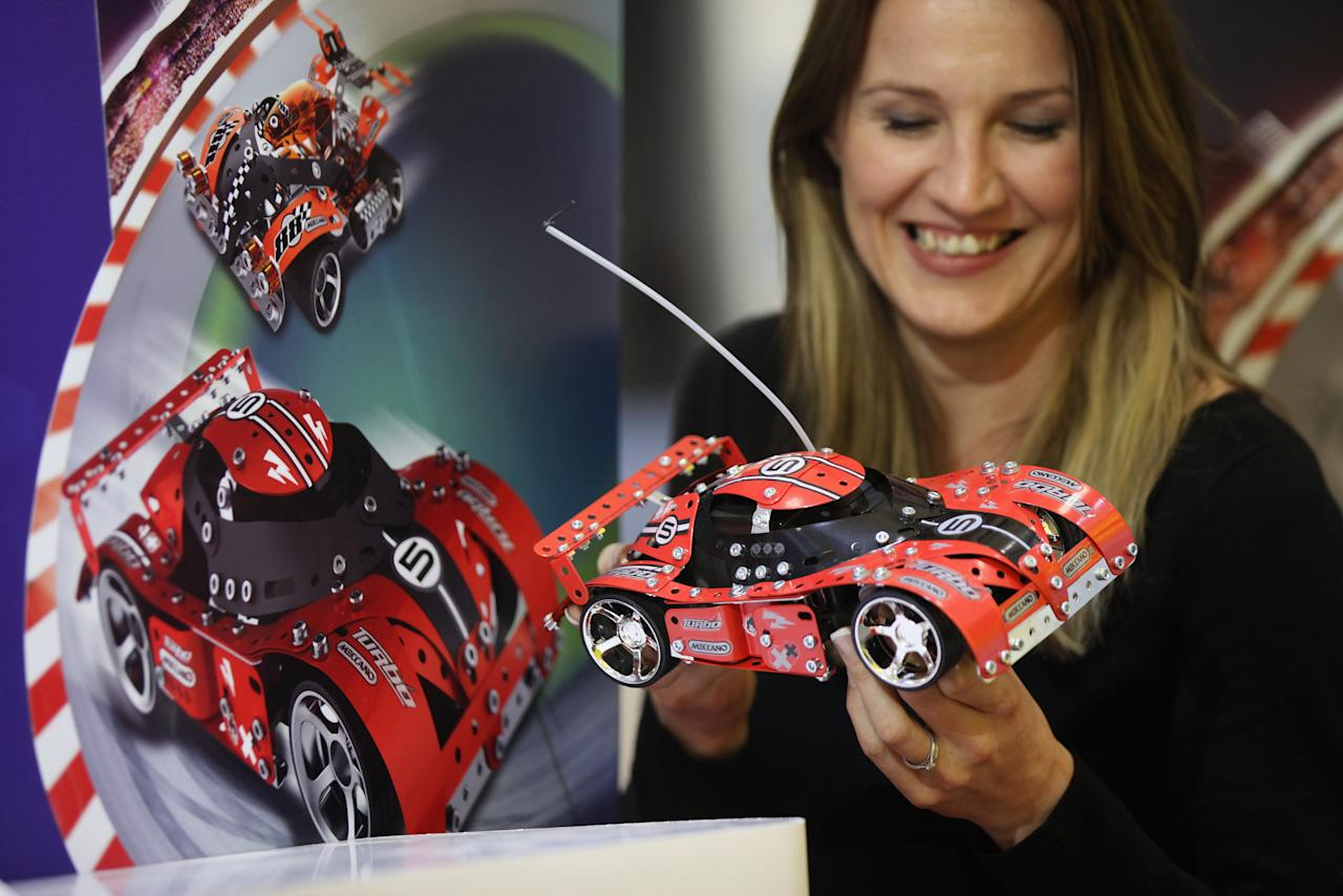 LONDON, ENGLAND - JANUARY 24:  A woman admires a Meccano racing car toy at the 2012 London Toy Fair, at Olympia Exhibition Centre on January 24, 2012 in London, England. The annual fair, which is organised by the British Toy and Hobby Association, brings together toy manufacturers with retailers from around the world.  (Photo by Oli Scarff/Getty Images)