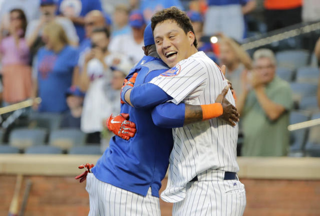 New York Mets' Wilmer Flores, right, hugs Jose Reyes after hitting a walk-off home run during the tenth inning in the first game of a baseball doubleheader against the Philadelphia Phillies Monday, July 9, 2018, in New York. The Mets won 4-3. (AP Photo/Frank Franklin II)