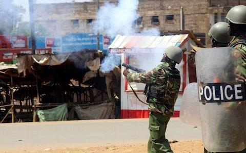 <span>A Kenyan riot policeman fires a tear gas canister toward demonstrators supporting opposition leader Raila Odinga</span>