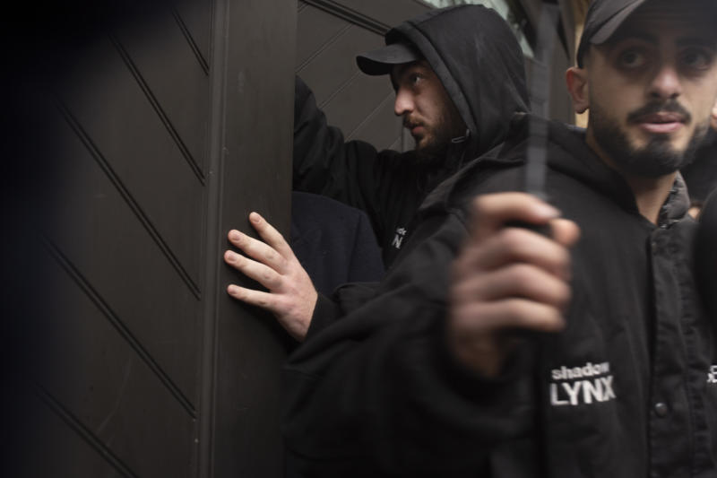 Private security guards secure a garage door to the home of former Nissan Chairman Carlos Ghosn in Beirut, Lebanon, Thursday, Jan. 2, 2020. Turkish authorities have detained seven people as part of an investigation into how Ghosn, who skipped bail in Japan, was able to flee to Lebanon via Istanbul, Turkish media reported Thursday. (AP Photo/Maya Alleruzzo)
