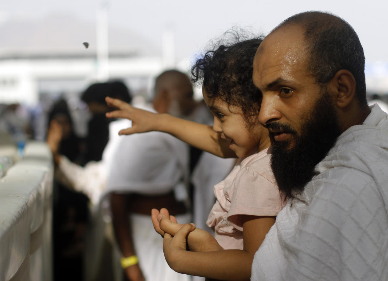 """A Muslim pilgrim carries his son as they cast stones at a pillar, symbolizing the stoning of Satan, in a ritual called """"Jamarat,"""" the last rite of the annual hajj, in the Mina neighborhood of Mecca, Saudi Arabia, Tuesday, Oct. 15, 2013. The 10th day of the Islamic lunar month of Dhul-Hijja, during the hajj, is the beginning of Eid al-Adha, the most important Islamic holiday, to mark the willingness of the Prophet Ibrahim, or Abraham to Christians and Jews, to sacrifice his son. (AP Photo/Amr Nabil)"""