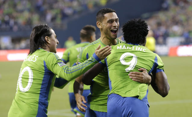 Seattle Sounders' Obafemi Martins, right, celebrates his goal against Real Salt Lake with teammates Mauro Rosales, left, and Lamar Neagle, center, in the first half of an MLS soccer match, Friday, Sept. 13, 2013, in Seattle. (AP Photo/Ted S. Warren)