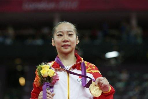 Gold medalist China's gymnast Deng Linlin poses on the podium