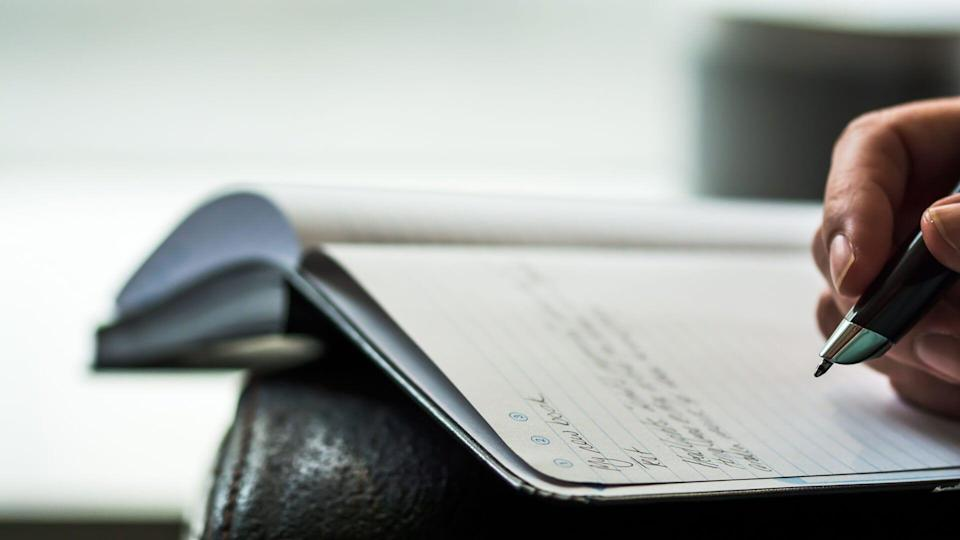 An author scribbles notes in a notebook with a smartpen - Image.
