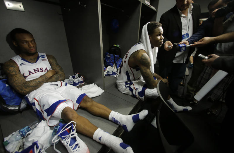 Kansas' Naadir Tharpe, left, and Ben McLemore right react in the lockeroom after losing 87-85 to Michigan in overtime of a regional semifinal game in the NCAA college basketball tournament, Friday, March 29, 2013, in Arlington, Texas. (AP Photo/Tony Gutierrez)