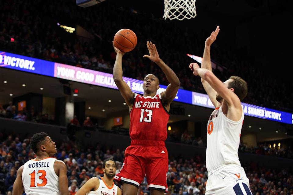 CHARLOTTESVILLE, VA - JANUARY 20: C.J. Bryce #13 of the North Carolina State Wolfpack shoots over Jay Huff #30 of the Virginia Cavaliers in the first half during a game at John Paul Jones Arena on January 20, 2020 in Charlottesville, Virginia.