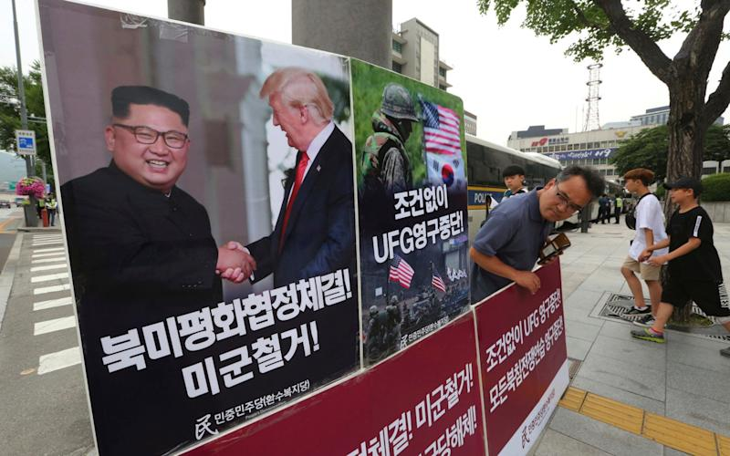A photo showing President Donald Trump and North Korean leader Kim Jong-un is displayed as a member of the People's Democratic Party protests against military exercises between the United States and South Korea in Seoul - AP