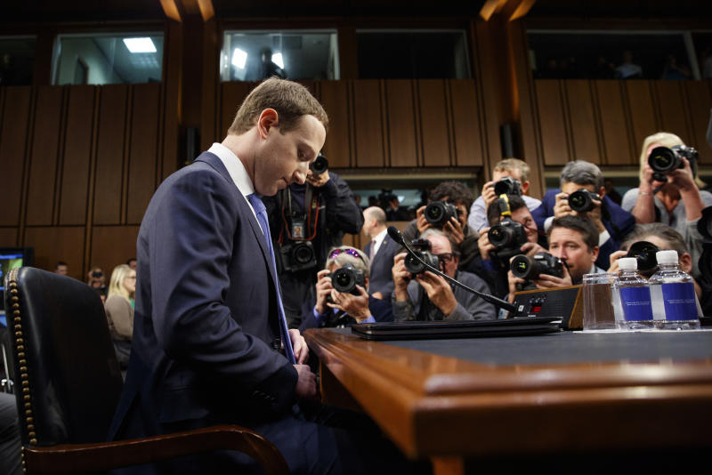 """FILE- In this April 10, 2018, file photo Facebook CEO Mark Zuckerberg adjusts his tie as he arrives to testify before a joint hearing of the Commerce and Judiciary Committees on Capitol Hill in Washington. Earlier this month Zuckerberg announced a new """"privacy-focused vision"""" for the company to focus on messaging instead of more public sharing, but he stayed mum on overhauling Facebook's privacy practices in its core business. (AP Photo/Carolyn Kaster, File)"""
