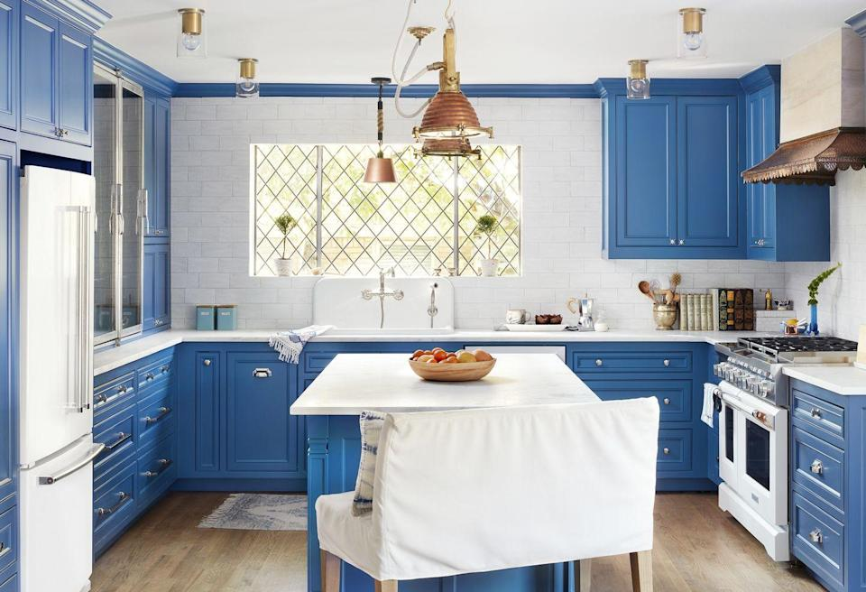 """<p>Distract the eye from low ceilings with a bold blue paint color on kitchen cabinets. Polished silver hardware shines against doors painted in <a href=""""https://www.benjaminmoore.com/en-us/color-overview/find-your-color/color/HC-159/philipsburg-blue?color=HC-159"""" rel=""""nofollow noopener"""" target=""""_blank"""" data-ylk=""""slk:Philipsburg Blue by Benjamin Moore"""" class=""""link rapid-noclick-resp"""">Philipsburg Blue by Benjamin Moore</a>.</p>"""