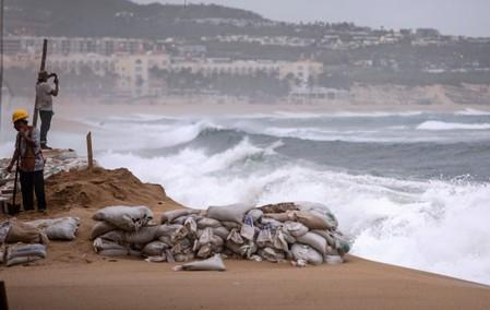 Workers are pictured at La Medano beach in Cabo San Lucas as Hurricane Lorena churns close to the southern tip of Mexico's Baja California