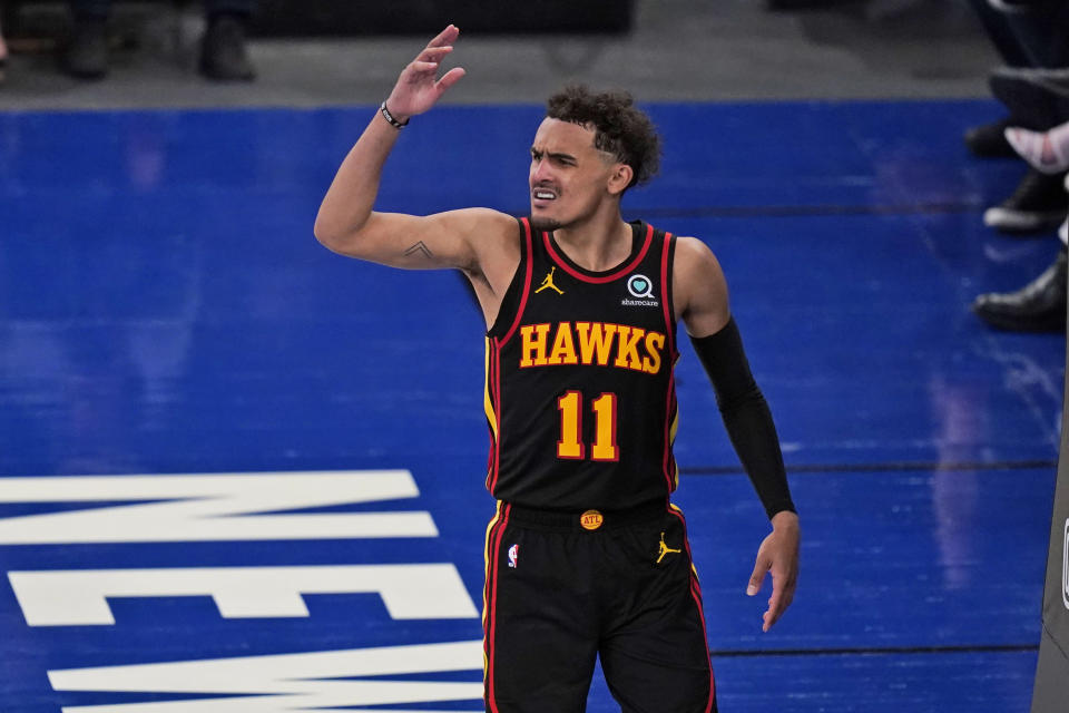 Trae Young reacts and throws an arm up in the air.