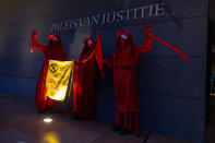 """Demonstrators hold a banner reading """"standing by and watching is no longer an option"""" outside the court building prior to the start of the court case of Milieudefensie, the Dutch arm of the Friends of the Earth environmental organization, against Shell in The Hague, Netherlands, Tuesday, Dec. 1, 2020. A landmark legal battle opened as climate change activists in the Netherlands go to court seeking an order for energy giant Shell to rein in its carbon emissions. (AP Photo/Peter Dejong)"""