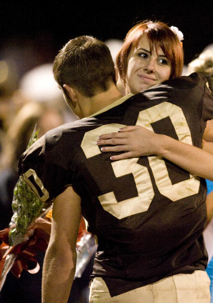 Sophomore homecoming representatives Whitney Kropp and Josh Awrey give each other a hug during the homecoming ceremony on the Ogemaw Heights High School football field Friday night, Sept. 28, 2012, in West Branch, Mich. Kropp was named to the homecoming court of the 800-student school earlier this month, but said she felt betrayed after some students suggested her selection was a joke. (AP Photo/Detroit News, John M. Galloway) DETROIT FREE PRESS OUT; HUFFINGTON POST OUT