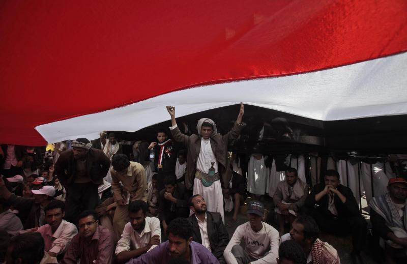 "FILE - In this Saturday, March 5, 2011 file photo, anti-government protestors take shelter from the sun under their national flag during a demonstration demanding the resignation of Yemeni President Ali Abdullah Saleh, in Sanaa, Yemen. Almost a quarter-century ago, a young American political scientist achieved global academic celebrity by proclaiming that the collapse of communism had ended the discussion on how to run societies, leaving ""Western liberal democracy as the final form of human government."" In Egypt and around the Middle East, after a summer of violence and upheaval, the discussion, however, is still going strong. And almost three years into the Arab Spring revolts, profound uncertainties remain. (AP Photo/Muhammed Muheisen, File)"