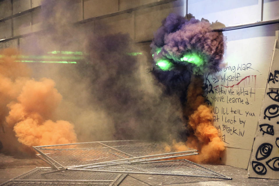 Smoke fills the street as police respond to protesters during a demonstration, Friday, July 17, 2020 in Portland, Ore. Militarized federal agents deployed by the president to Portland, fired tear gas against protesters again overnight as the city's mayor demanded that the agents be removed and as the state's attorney general vowed to seek a restraining order against them. (Dave Killen/The Oregonian via AP)