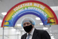 FILE - In this Saturday, Feb. 13, 2021 file photo, Britain's Prime Minister Boris Johnson, wearing a face mask to prevent the spread of the coronavirus, visits a PPE manufacturing facility during a visit to the north east of England, in Seaton Delaval, England. British Prime Minister Boris Johnson is expected to confirm Monday June 14, 2021, that the next planned relaxation of coronavirus restrictions in England will be delayed as a result of the spread of the delta variant first identified in India. (AP Photo/Scott Heppell, Pool, File)