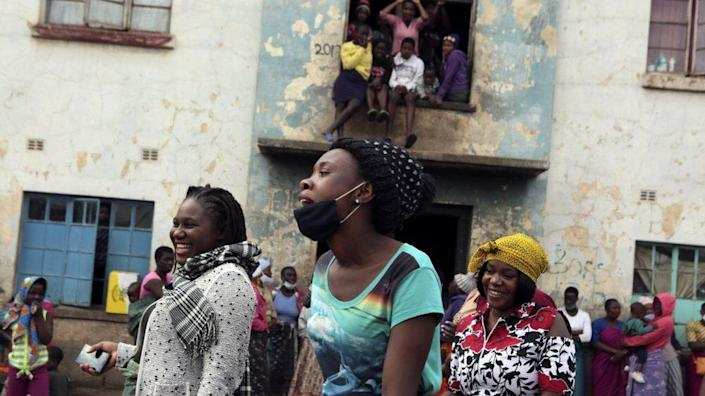 Women share a light moment while attending a social gathering in a poor neighborhood in Mbare, Harare, Zimbabwe, Friday, Sept,18, 2020. (AP Photo/Tsvangirayi Mukwazhi)