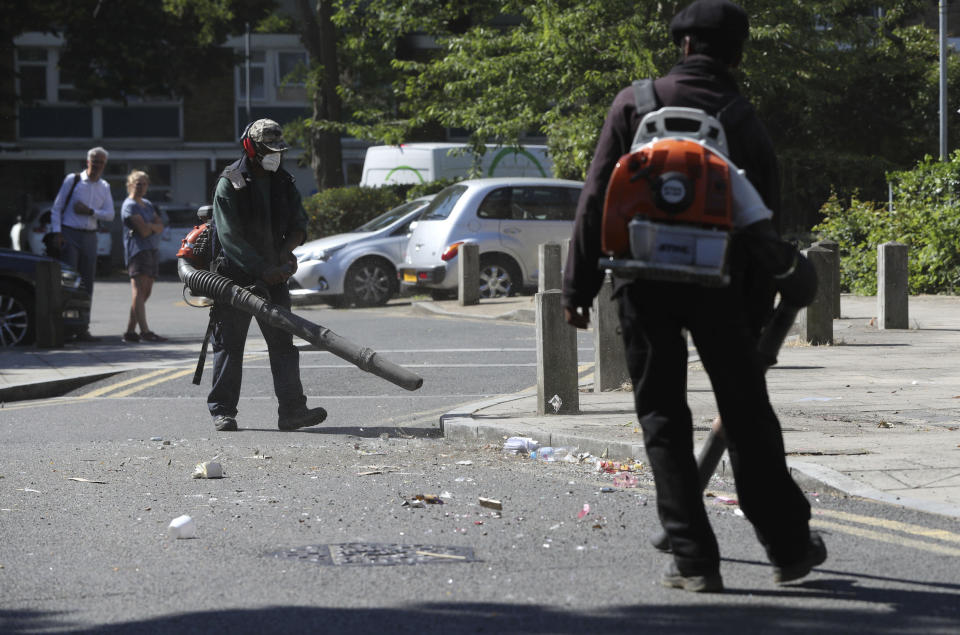Volunteers clean up following violent confrontations with police took place overnight, in the Brixton area of London, Thursday June 25, 2020. Authorities have reported fifteen officers were injured and four people were arrested following the incident. (Jonathan Brady/PA via AP)