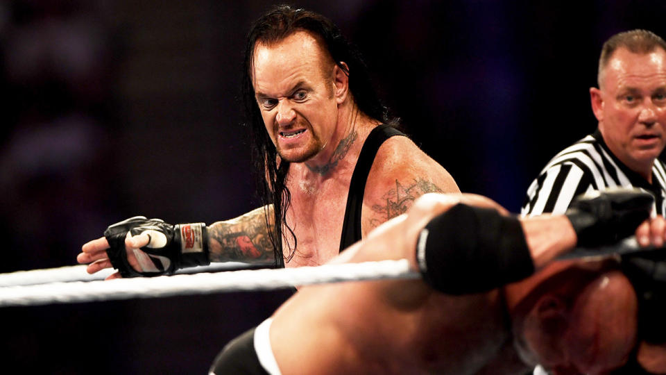The Undertaker, Mark Calaway, sets up for the chokeslam.