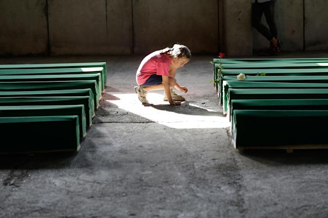 <p>A Bosnian girl reads a name tag on a coffin among 71 caskets displayed at the memorial centre of Potocari near Srebrenica, 150 kms north east of Sarajevo, Bosnia, Monday, July 10, 2017, prior to their burial scheduled for Tuesday. (Photo: Amel Emric/AP) </p>