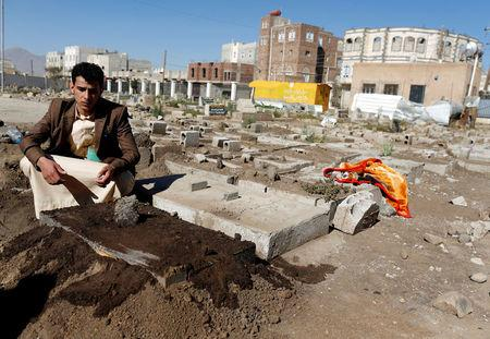 Akram al-Bahshani sits next to the grave of his conjoined twins AbdulKhaleq and AbdulRahim, after their burial at a graveyard in Sanaa