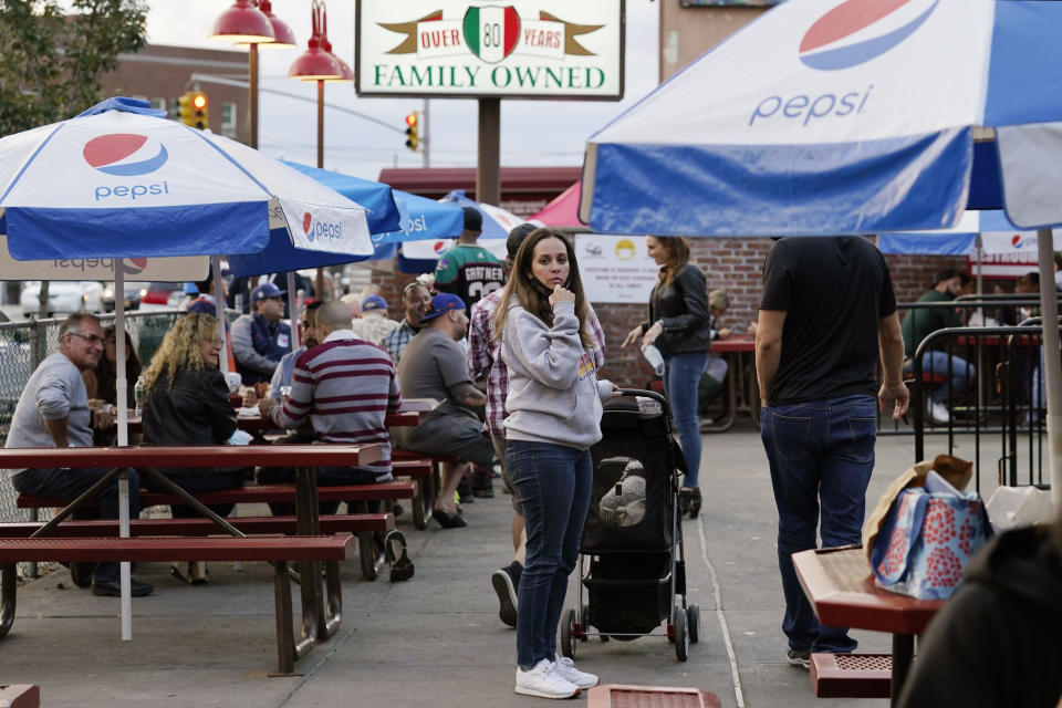 A woman waits in line at L&B Spumoni Gardens during the dinner hour, Sunday, Oct. 4, 2020, in the Bensonhurst/Gravesend section of the Brooklyn borough of New York The popular Italian eatery, located in an area where coronavirus cases are rising, may be forced to close down its outdoor dining area this week if restrictions announced by New York's mayor Sunday go into place. Mayor Bill de Blasio said that he has asked the state for permission to close schools and reinstate restrictions on nonessential businesses in several New York neighborhoods, including this one, because of a resurgence of the coronavirus. (AP Photo/Kathy Willens)