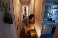 Ines Alcolea arranges moving boxes before leaving her rented apartment in Madrid