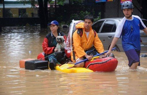 Manila residents are evacuated from a suburb of Manila. Philippine authorities have appealed for help in getting relief to two million people affected by deadly floods in and around the capital, warning that evacuation centres were overwhelmed