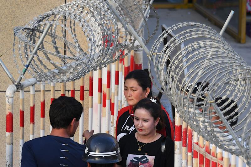 Uighur women are stopped by police as they enter Xinjiang (AFP via Getty Images)