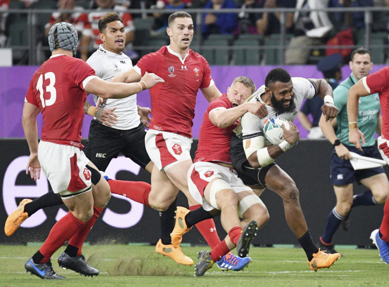 Fiji's Waisea Nayacalevu is tackled by the Welsh defence during the Rugby World Cup Pool D game at Oita Stadium between Wales and Fiji in Oita, Japan, Wednesday, Oct. 9, 2019. (Kyoto via AP)/Kyodo News via AP)