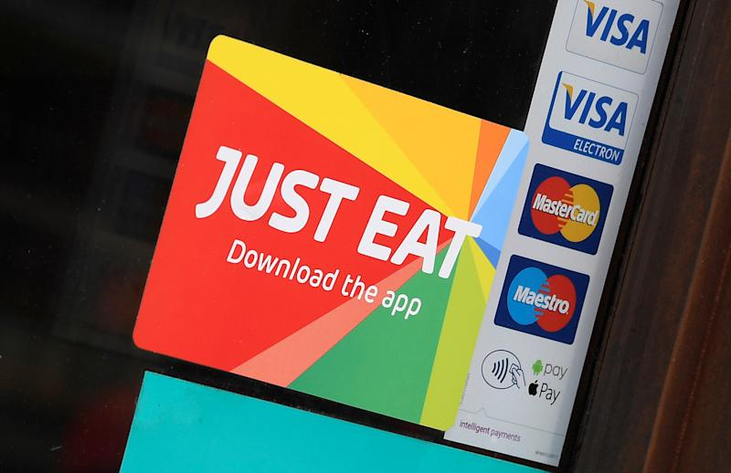 Signage for Just Eat is seen on the window of a restaurant in London, Britain, August 5, 2019. REUTERS/Toby Melville.