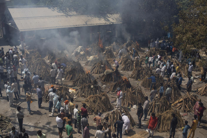 Multiple funeral pyres of those who died of COVID-19 burn at a ground that has been converted into a crematorium for the mass cremation of coronavirus victims, in New Delhi, India, Saturday, April 24, 2021. Delhi has been cremating so many bodies of coronavirus victims that authorities are getting requests to start cutting down trees in city parks, as a second record surge has brought India's tattered healthcare system to its knees. (AP Photo/Altaf Qadri)