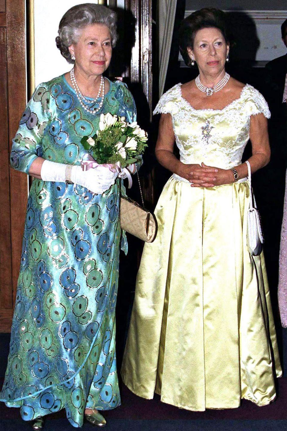 <p>The queen wore a blue and green printed satin dress, white gloves, a multi-strand pearl necklace, and a pair of earrings with Princess Margaret for a concert at The Royal College Of Music.</p>