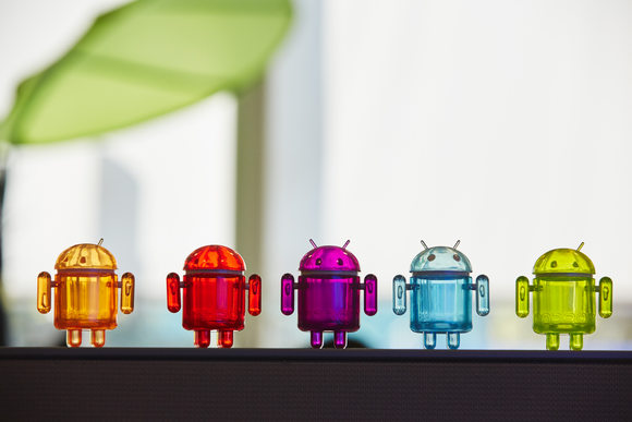 Five plastic toy versions of Alphabet's Android robot lined up in a row.