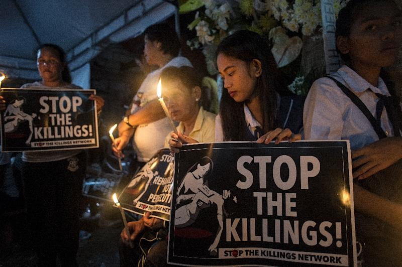 Classmates of Kian delos Santos light candles at his wake in August 2017
