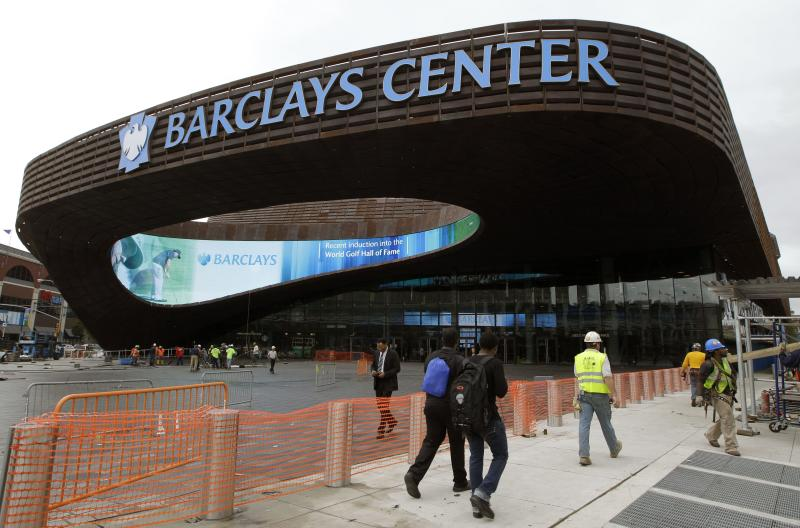 Pedestrians pass the main entrance to the Barclays Arena in New York, Thursday, Sept. 20, 2012 as workmen complete their cleanup for Friday's ribbon-cutting ceremony. A new chapter in Brooklyn's history Friday when the Brooklyn Nets new arena will open, just across the street from the spot where the Dodgers owner once tried to build a baseball stadium that never saw the light of day. (AP Photo/Kathy Willens)