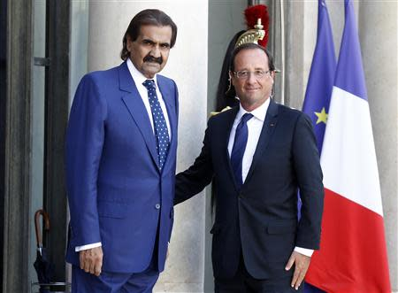 France's President Francois Hollande (R) welcomes Emir of Qatar Sheikh Hamad bin Khalifa al-Thani as he arrives for a meeting at the Elysee Palace in Paris in this August 22, 2012 file photo. REUTERS/Jacky Naegelen/Files