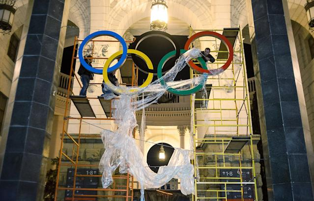 In this Monday, Oct. 28, 2013 photo, workers are fixing the Olympic emblem at an entrance to the railway station of Russia's Black Sea resort of Sochi, Russia. Russia starts 100 day count down on Tuesday, Oct. 29, 2013 for the 2014 Winter Olympic Games. (AP Photo/Lesya Polyakova)