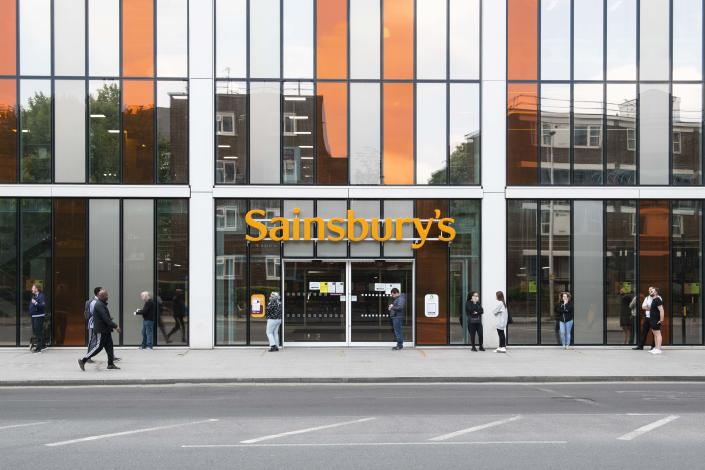 Members of the public respect social distancing rules and queue outside Sainsbury's in Vauxhall, London. (AP)