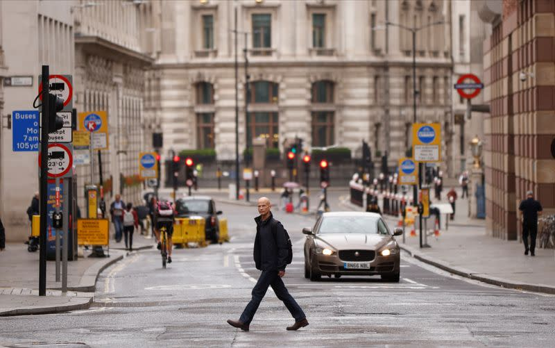 A man crosses the road in the City of London financial district amid the outbreak of the coronavirus disease (COVID-19)